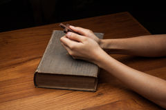 Hands folded in prayer over Holy Bible Stock Images