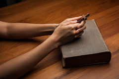 Hands folded in prayer over Holy Bible Royalty Free Stock Photos