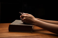 Hands folded in prayer over Holy Bible Stock Photo