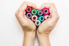 Hands folded in the shape of a heart with spools of thread. royalty free stock images