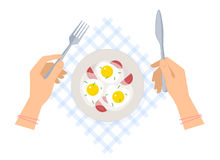 Hands with fork and knife, ceramic plate with scrambled eggs. Stock Photography