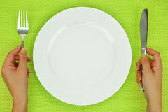 Hands with fork and knife and empty plate Royalty Free Stock Photos