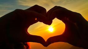 Hands in the form of heart against dramatic golden sunrise Royalty Free Stock Photos