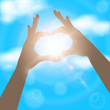Hands in the form of heart on the background of blue sunny sky. Royalty Free Stock Images