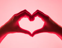 Hands in the form of heart red background. heart symbol with hand. valentines day card. Woman`s hands silhouette in form of heart. Stock Photo