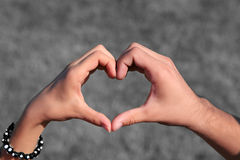 Hands forming heart. Male and female hands forming heart shape. To highlight female hand it has a bracelet. With dark gray background Stock Images
