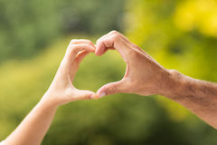 Hands forming heart Stock Images