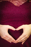 Hands forming heart on female belly Royalty Free Stock Photography