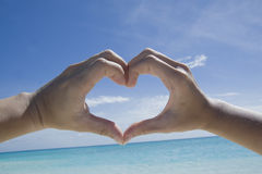 Hands forming a heart on maldives beach Royalty Free Stock Image