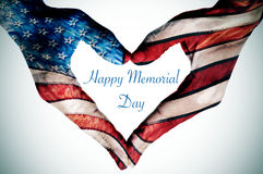Hands forming a heart patterned and text happy memorial day. The text happy memorial day written in the blank space of a heart sign, made with the hands of a Royalty Free Stock Images