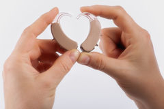 Hands forming a heart shape from hearing aids Royalty Free Stock Photography