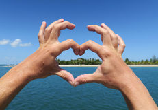 Hands forming heart. Tropical holiday concept with blue water Stock Images