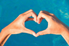 Hands forming a heart on water background. Hands forming a heart on blue water background Royalty Free Stock Photo
