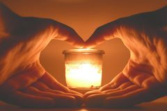 Hands forming a hearth in front of the light of a candle. The whole photo is under soft orange and pink light that gives a warming feeling Stock Image