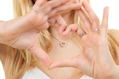 Hands forming love heart shape. Hands of blond teenager forming love heart shape in front of love heart necklace, white background Stock Photography