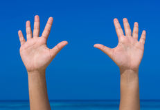 Hands forming raise/agree with blue sea and sky Royalty Free Stock Photos
