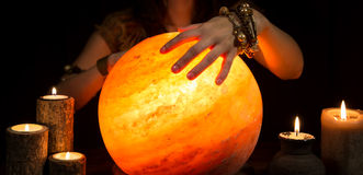Hands of a fortune teller, a shining crystal ball and candles Stock Photo