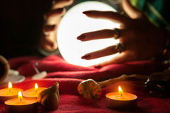 Hands of fortune teller witch in front of crystal ball Stock Image
