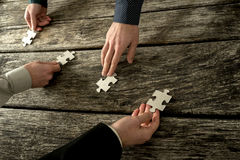 Hands of four businessman placing each a piece of puzzle in a ro Stock Photos