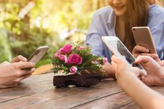 Hands of four teenagers use smartphone together in cafe royalty free stock photography
