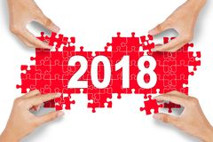 Four people arranging puzzle with number 2018 Royalty Free Stock Images