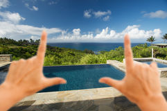 Hands Framing Oceanview Pool and Patio. Hands Framing Pool and Hot Tub Overlooking the Ocean Stock Photos