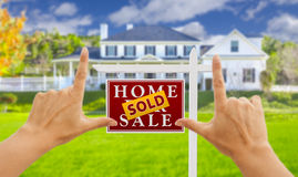Hands Framing Sold For Sale Real Estate Sign and House. Female Hands Framing Sold Home For Sale Real Estate Sign in Front of New House royalty free stock image