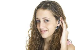 Hands-Free. A pretty female talks on a hands-free wireless headset Royalty Free Stock Images