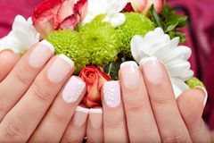 Hands with french manicured nails. Hands with beautiful short french manicured nails and a bouquet of flowers Stock Images
