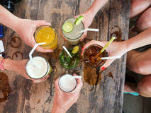 Hands of friends in circle holding cocktails Royalty Free Stock Images