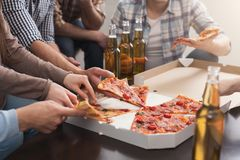 Hands of friends taking slices of tasty pizza at home Royalty Free Stock Photography