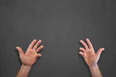 Hands in front of chalkboard. Mans hands on a chalkboard Royalty Free Stock Photos