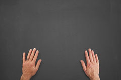 Hands in front of chalkboard. Mans hands on a chalkboard Royalty Free Stock Photography