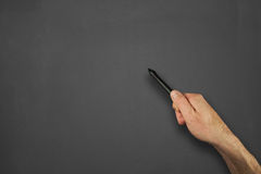 Hands in front of chalkboard. Mans hand pointing to a blank message on a chalkboard Royalty Free Stock Image