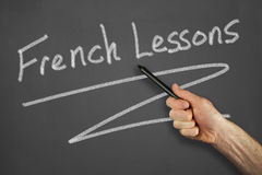 Hands in front of chalkboard. Mans hand pointing to a french lessons message on a chalkboard Royalty Free Stock Image