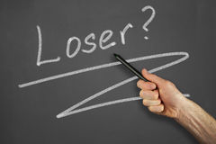 Hands in front of chalkboard. Mans hand pointing to a loser message on a chalkboard Stock Images