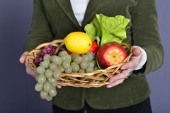 Hands with a fruit. Ladies hands with a basket full of healthy fruit Royalty Free Stock Photo