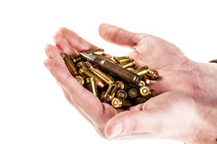 Hands full of ammo. A heap of 9mm pistol bullets holded by human hands isolated over a white backgrounds Royalty Free Stock Images
