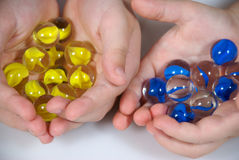 Hands full of marbles. Children's hands full of colorful marbles Stock Photography
