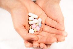 Hands full of medicines. Hands with tablets, pills and medicines on a white background Royalty Free Stock Photo