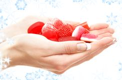 Hands full of red bonbons Royalty Free Stock Photography