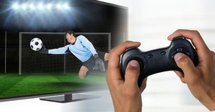 Hands with game controller in front of tv screen with goalkeeper reaching out the ball. Digital composite of Hands with game controller in front of tv screen Royalty Free Stock Images