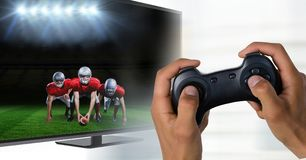 Hands with game controller in front of tv screen with goalkeeper reaching out the ball stock photography