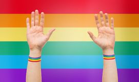 Hands with gay pride rainbow wristbands. Lgbt, same-sex relationships and homosexual concept - close up of male hands wearing gay pride awareness wristbands over Royalty Free Stock Image
