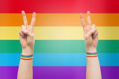 Hands with gay pride rainbow wristbands make peace. Lgbt, same-sex relationships and homosexual concept - close up of male hands wearing gay pride awareness Stock Image