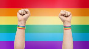 Hands with gay pride rainbow wristbands shows fist. Lgbt, same-sex relationships and homosexual concept - close up of male hands wearing gay pride awareness Stock Image