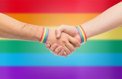 Hands with gay pride wristbands make handshake royalty free stock photography
