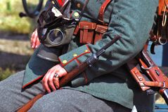 Hands of a German soldier-reenactor holding a gun. Stock Image