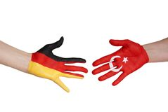 Hands with german and turkey flag Royalty Free Stock Images