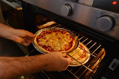 Hands getting out from the oven homemade pizza Royalty Free Stock Photos